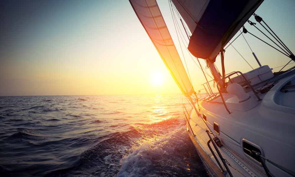 Sail boat gliding in open sea at sunset
